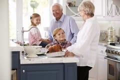Children And Grandparents Make Roast Turkey Meal In Kitchen Stock Image