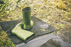 Children green boots left in the rainy weather outdoor one is fi Royalty Free Stock Photography