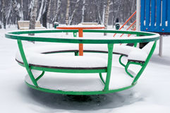 Children green round swing in snow Stock Image