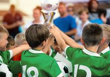 Children in Green Sportswear Celebrating Sport Success. Kids Raising Golden Cup for Winning Sports Team. Children in Green Sportswear Celebrating Sport Success royalty free stock photography