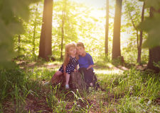 Children in Green Sunny Nature Woods. Two young children are sitting on a tree stump in the sunshine with green leaves in the woods for a relaxation or nature stock image