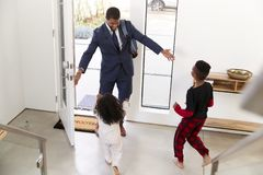 Children Greeting And Hugging Working Businessman Father As He Returns Home From Work royalty free stock photo
