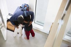 Children Greeting And Hugging Working Businessman Mother As She Returns Home From Work stock photo