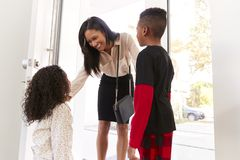 Children Greeting And Hugging Working Businesswoman Mother As She Returns Home From Work royalty free stock image