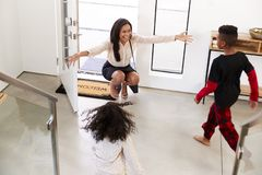 Children Greeting And Hugging Working Businesswoman Mother As She Returns Home From Work stock photo