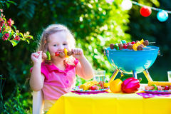 Children grilling meat. Family camping and enjoying BBQ. Little girl at barbecue preparing steaks, kebab and corn. Kids eating grill and healthy vegetable meal Royalty Free Stock Image