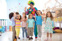 Children group with clown celebrating birthday party. In daycare royalty free stock photography