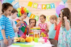 Children group with clown celebrating birthday party. In daycare. Happy kids hold each other`s hands stock image