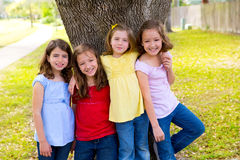 Children group friend girls playing on tree. Children group friend girls friends playing on tree trunk at the park outdoor Royalty Free Stock Photos
