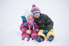 Children group  having fun and play together in fresh snow Stock Photos