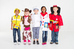 Children group play. Group of cute little children play in various workers uniform or work wear, studio shot