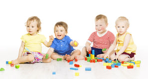Children group playing toy blocks. Small Kids on w