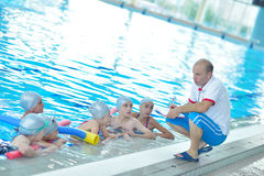 Children group at swimming pool. Group of happy kids children at swimming pool class learning to swim stock images