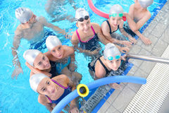 Children group at swimming pool. Group of happy kids children at swimming pool class learning to swim royalty free stock photos