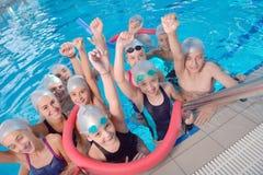 Children group at swimming pool. Group of happy kids children at swimming pool class learning to swim stock photo