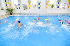 Children Group At Swimming Pool. Shot of children& x27;s group swimming freestyle at swimming lesson. Kindergarten children in swimming lesson. Preschoolers royalty free stock images