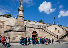 Children in group of tourists walk past the historical buildings Royalty Free Stock Photo
