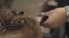 Children hairstylist cutting little boy with electrical razor in hairdressing salon. Haidresser doing kid hairstyle with. Electric shaver in children barber stock video footage