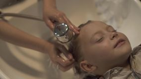 Children hairstylist washing hair with shampoo to little boy in barber salon. Close up wash children head in barber shop. Male hairdresser washing head to stock video footage