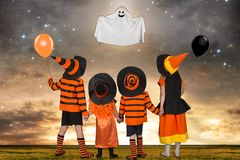 Children in Halloween costumes look at the flying Ghost. stock photography