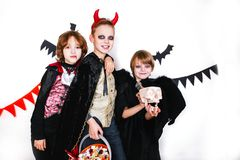 Children in halloween costumes show funny faces . Stock Photos