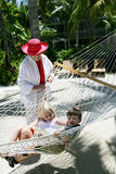Children in hammock. Two children in a hammock, their smiling grandmother standing looking after them Stock Photography