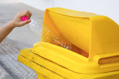 Children hand dropping used bottle in the trash Royalty Free Stock Photo