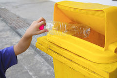Children hand dropping used bottle in the trash Royalty Free Stock Photos
