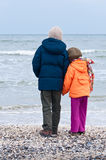 Children hand in hand looking at winter sea Stock Photos