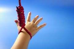 Children hand hanged on red thread Royalty Free Stock Photo