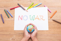 Children hand is holding globe model and paper NO WAR in white Royalty Free Stock Image