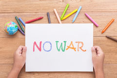 Children hand is holding paper NO WAR in white paper with writ Stock Images