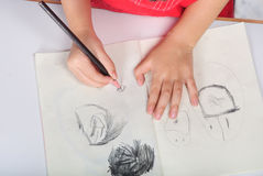 Children hand with pencil draws and sketchs many faces Stock Images