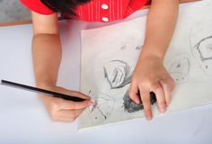 Children hand with pencil draws and sketchs many faces Royalty Free Stock Photos