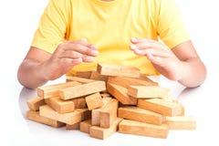 Children hand protect blocks wood game (jenga) isolated on white Stock Image
