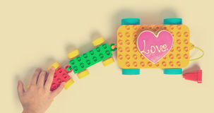 Children hand pulling colorful love train toy block. A child hand pulling colorful love train toy block Stock Photography