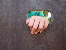 Children hand with small fingers through hole in wooden climbing wall ladder on kids playground Stock Image