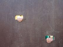 Children hand with small fingers through hole in wooden climbing wall ladder on kids playground Royalty Free Stock Photos