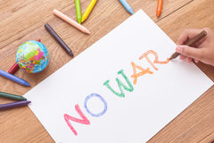Children hand is writing NO WAR in white paper with color cray Stock Image