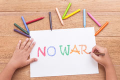Children hand is writing NO WAR in white paper with color cray Stock Images