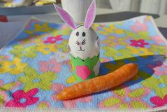 Children handmade: Easter bunny with carrot. Easter bunny made of an egg shell with carrot on the flower background Stock Image