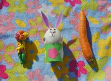 Children handmade: Easter bunny with flowers and carrot. Easter bunny made of an egg shell with plasticine flowers and carrot on the flower background Stock Photos