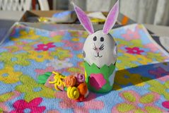 Children handmade: Easter bunny with flowers. Easter bunny made of an egg shell with plasticine flowers on the flower background Stock Photo