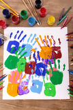 Children handprints and art equipment, art and craft class, school desk, classroom. Painted handprints with art and craft equipment on a school table royalty free stock photo