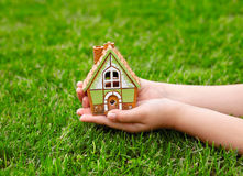 Children hands hold a house on a background of green grass Royalty Free Stock Image