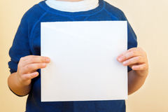 Children hands hold white paper blank Royalty Free Stock Photography