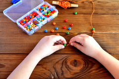 Children hands holding beads and cord. Baby sensory game Stock Photos