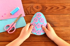Children hands holding a felt Easter egg. Scissors, thread, needle, pins Royalty Free Stock Photos