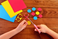 Children hands holding the scissors and paper and cut out the circle. Sheets of paper, paper circles on a brown wooden background Royalty Free Stock Image