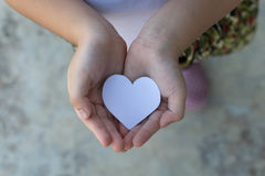Children hands holding small model of heart and family Royalty Free Stock Image